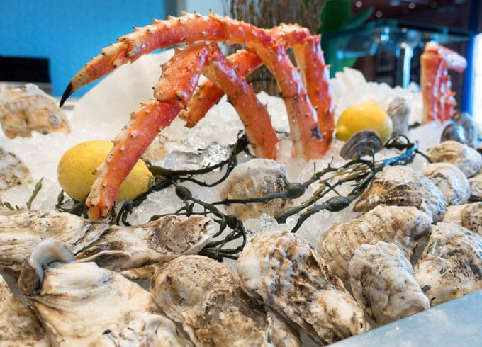 oysters and king crab legs on ice with lemons and seaweed