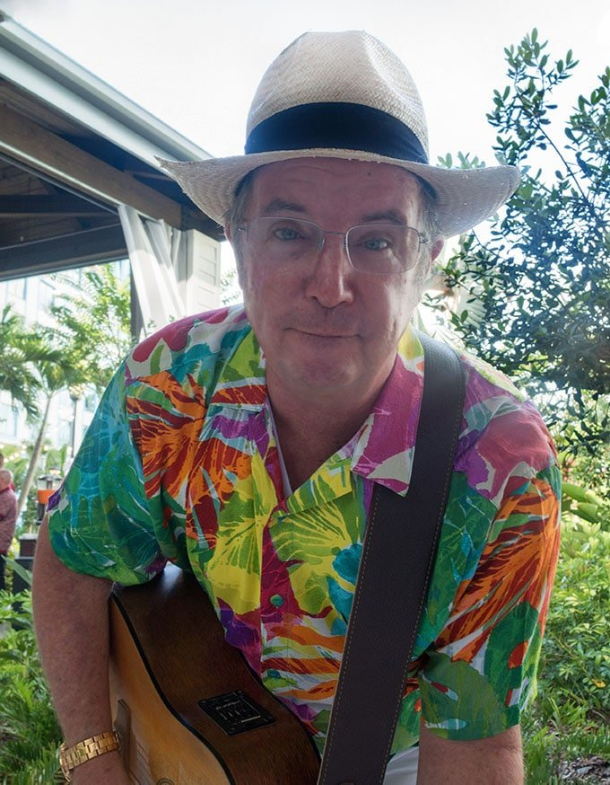 man in a brightly colored Hawaiian shirt with a guitar and straw hat