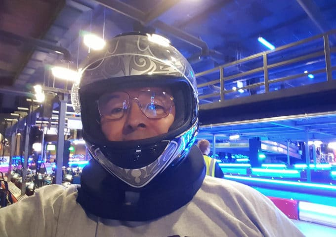 Chef Dennis in a racing helmet at a go kart track