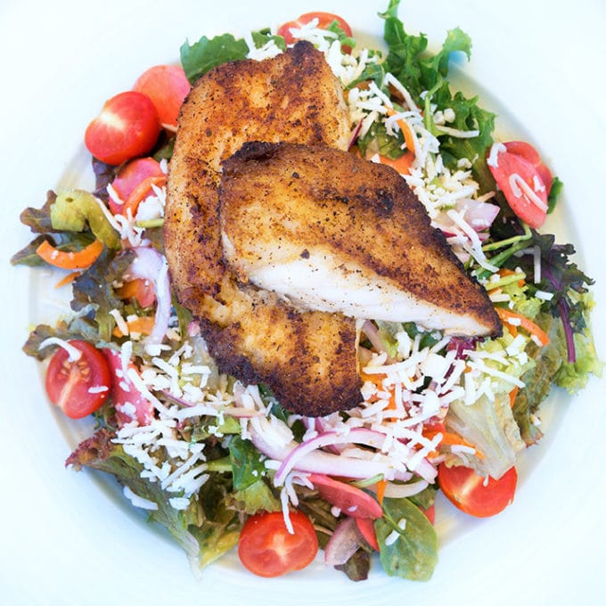 blackened fish salad on a white plate
