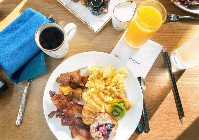breakfast plate with eggs, potatoes, bacon and a croissant. Coffee and orange juice on the table