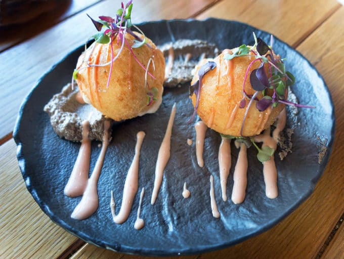 fried dough balls stuffed with cheese sitting on a black plate on a wooden table.