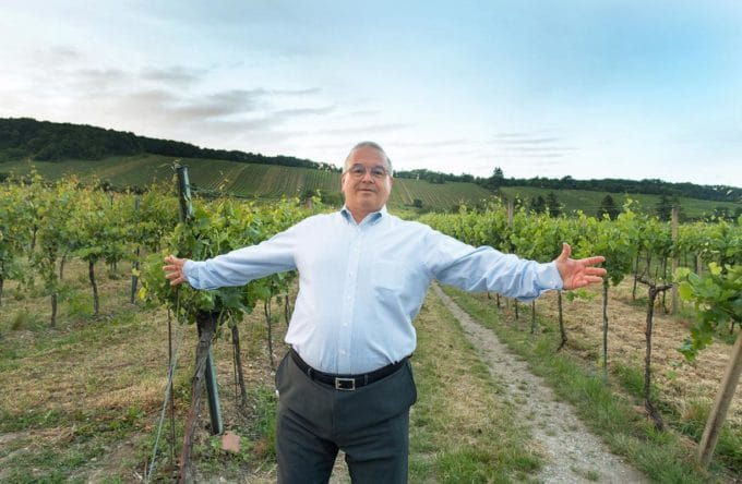 Chef Dennis with his arms outstretched in a vineyard in the Vienna Woods, Austria