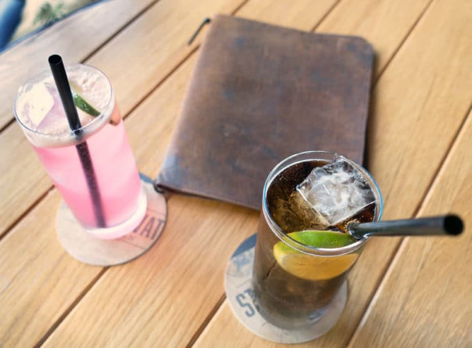 cuba libre and pink punch in glasses with straws on a wood table with a leather menu