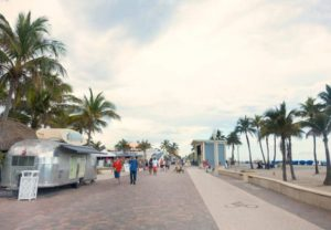 boardwalk with airstream food truck on one side with palm trees and beach on the other side