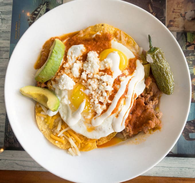 fried egg on top of tortillas with cheese, enchilada sauce and refried beans served on a white plate with avocado and jalapeno