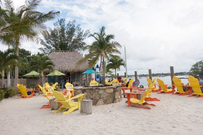 colorful Adirondack chairs with a fire pit on a beach with palm trees and a tiki hut