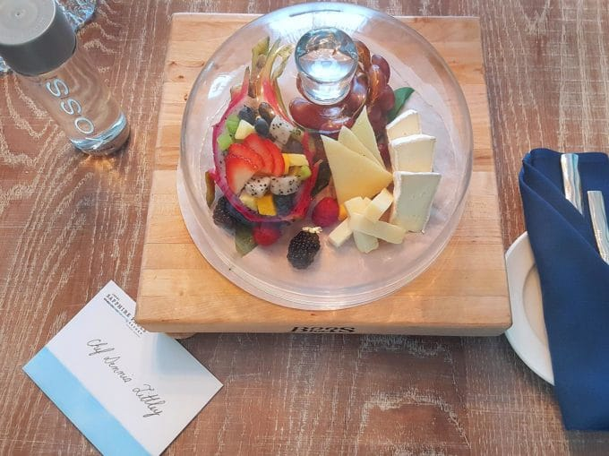 cheese and fruit on a cutting board under a glass dome. Sitting on a table with a blue napkin with silverware and a card