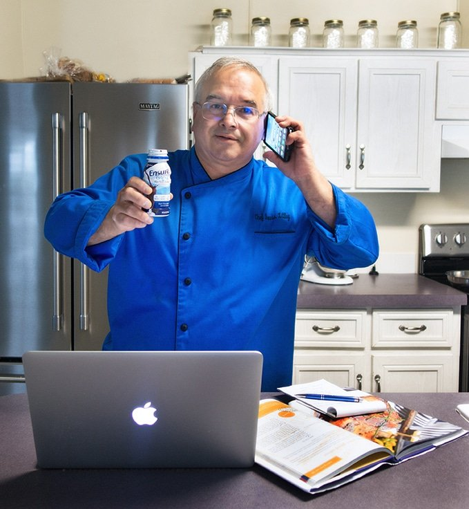 Chef Dennis with a laptop, phone and cookbook in his kitchen drinking Ensure