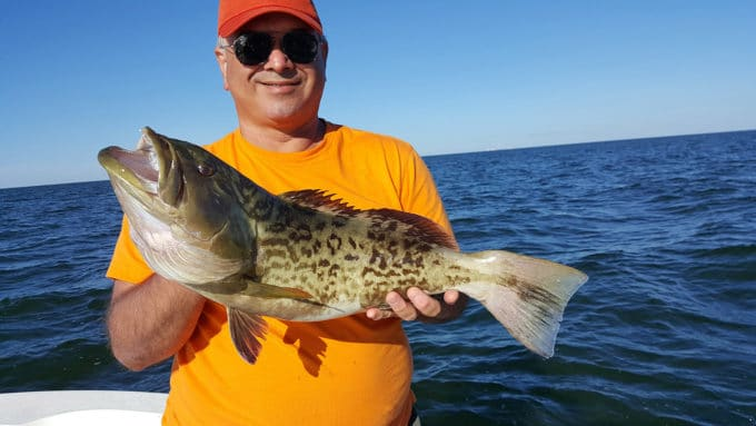 Chef Dennis holding a large Grouper on a boat in the gulf of Mexico