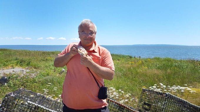 Chef Dennis holding a lobster roll in front of lobster traps with a view of the bay of fundy