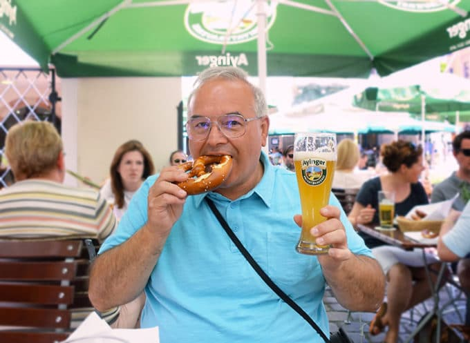 Chef Dennis eating a pretzel and holding a beer in Munich