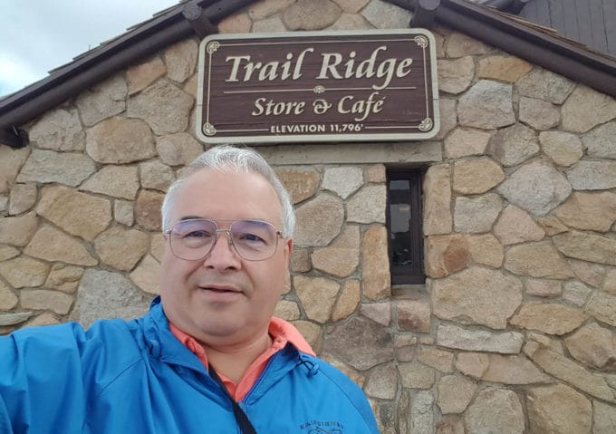 Chef Dennis standing in front of a stone building with a sign saying elevation 11,796 in Rocky Mountain National Park