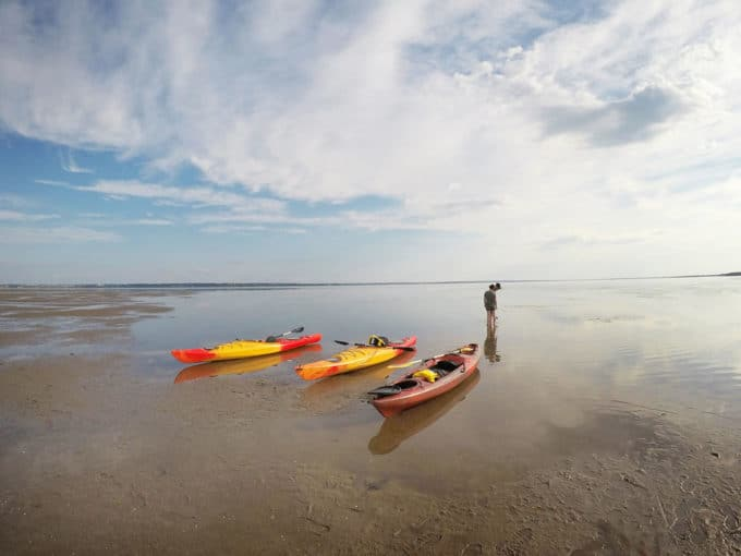 Kayaks on the mud flats of Caraquet, with one person looking out into the distance.