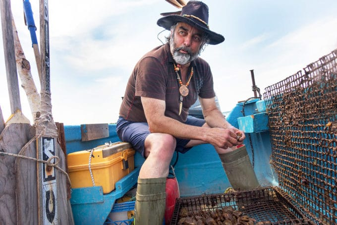 Mixed blood Acadian Oyster fisherman wearing a hat with a feather on his boat holding live oysters