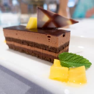 Chocolate mousse cake with fruit and a mint leave served on a white plate