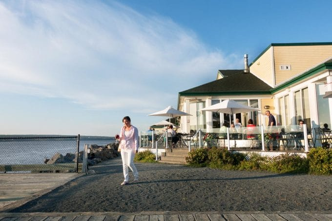 woman walking outside of a yellow building on the Mirimachi river in New Brunswick