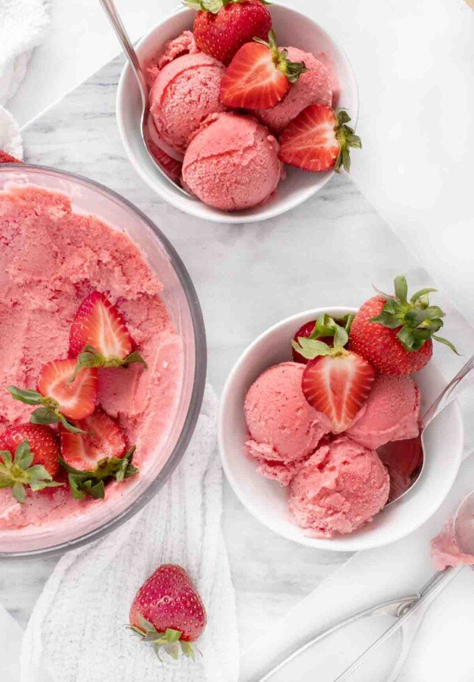 overhead view of 2 bowls of scoops of strawberry gelato next to container of frozen gelato