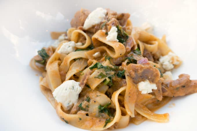 tagliatelli with pulled duck breast in a rosa sauce with chunks of goat cheese served in a white bowl