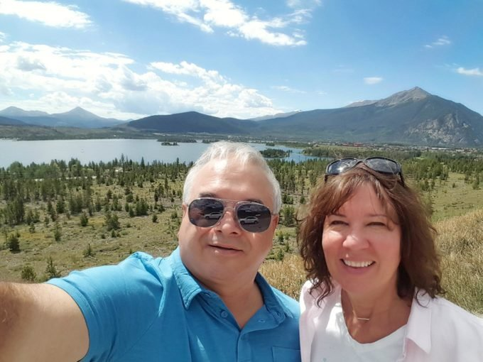 chef dennis and lisa in front of a lake and mountain range in Colorado