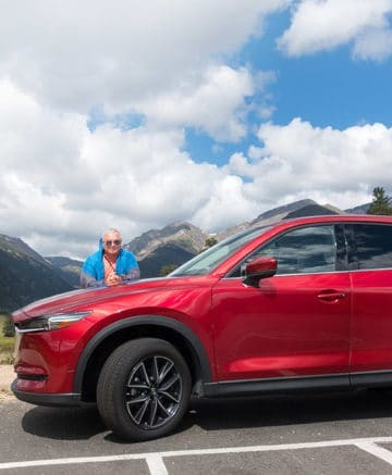Chef Dennis behind a Soul Red Mazda CX-5 with the Rocky Mountains in the background