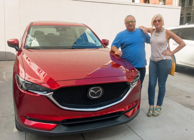 Chef Dennis and Mia Voss next to a Soul REd Mazda CX-5 in a parking lot