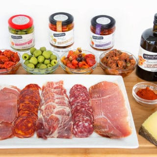 Hemisfares brand cured meats on a white tray with olives, tapenade and other ingredients on a wooden cutting board