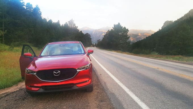 Soul Red Mazda CX-5 on the side of the road with the Rocky Mountains in the background