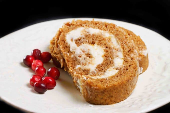 2 slices of pumpkin roll on a white plate with cranberries on a black background