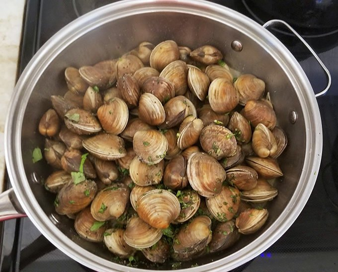 clams in large pan with seasonings preparing to be steamed