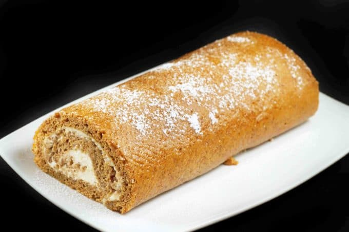 long view of pumpkin roll on a white platter on a black background