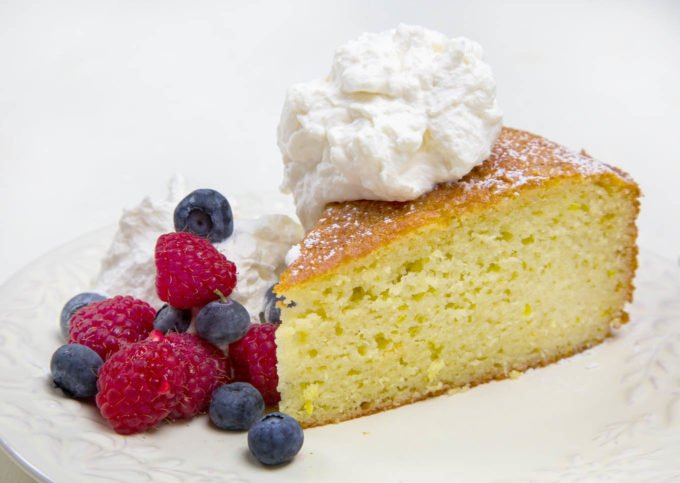 slice of yogurt cake with raspberries and blueberries topped with whipped cream on a white plate