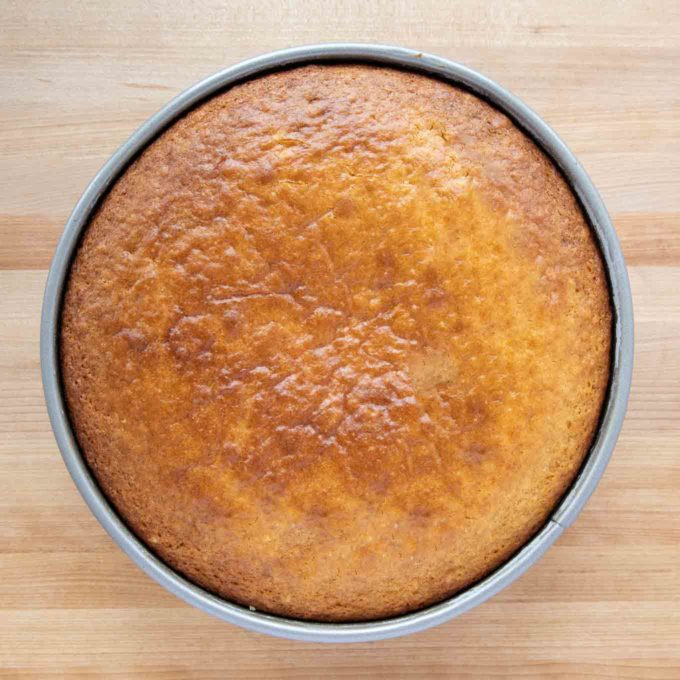 golden brown cake in the pan on a wooden cutting board