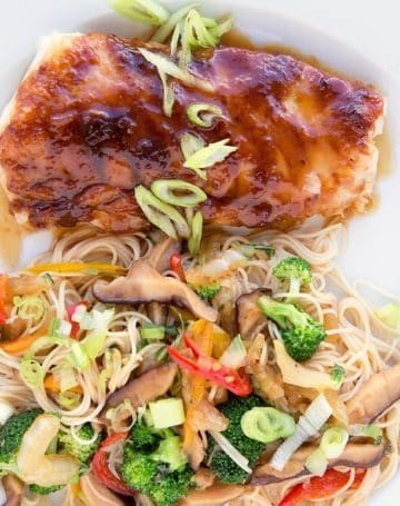 miso glazed cod with stirfried vegetables over noodles on a white plate