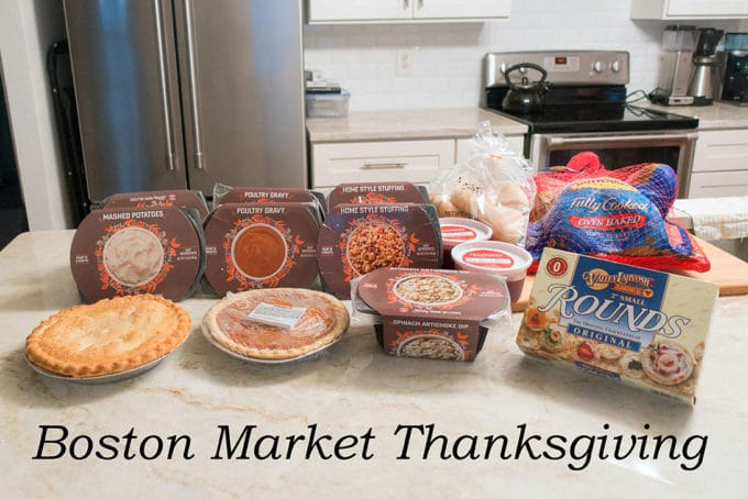 contents of Boston Market Thanksgiving box sitting on a countertop in a white kitchen. Including packages of a whole roasted turkey, stuffing, mashed potatoes, gravy, cranberry sauce, rolls , crackers and an artichoke dip