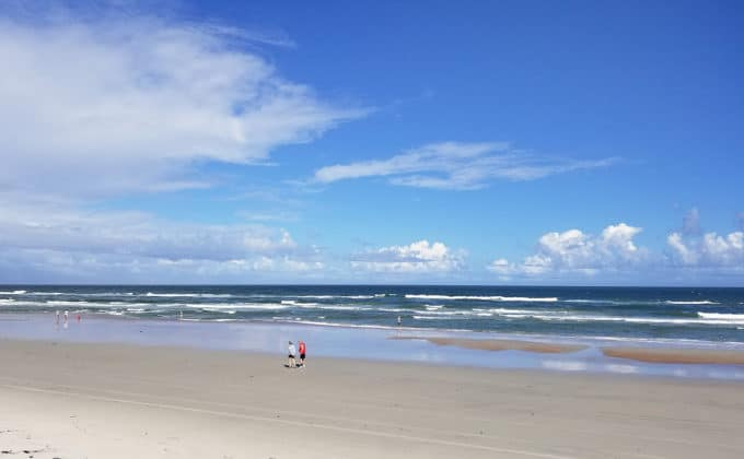 people walking on Daytona Beach by the ocean with beautiful blue skies and puffy white clouds