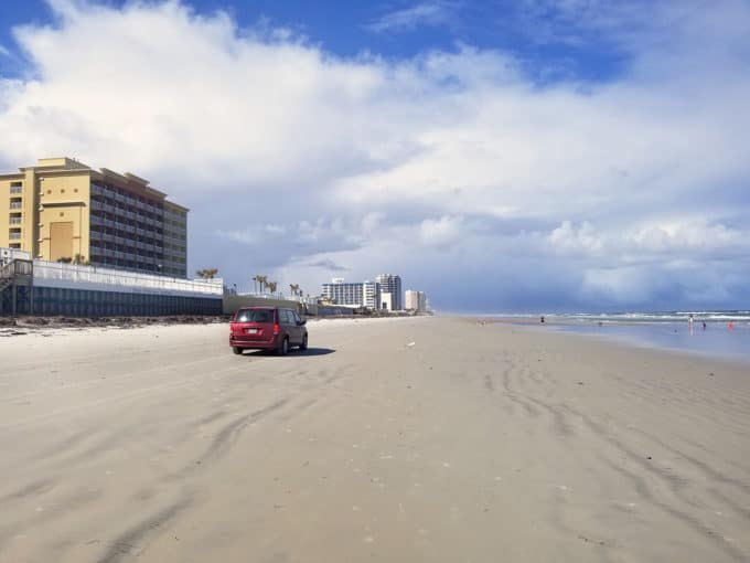 car driving on Daytona Beach on a perfect blue sky day