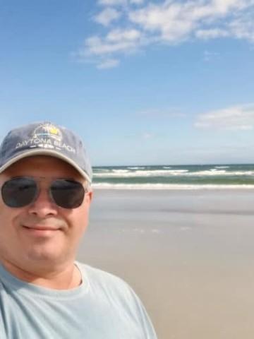 Chef Dennis at Daytona Beach in front of the ocean wearing a Daytona beach ball cap and sunglasses