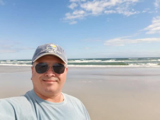 Chef Dennis at Daytona Beach in front of the ocean wearing a Daytona beach ball cap and sunglasses