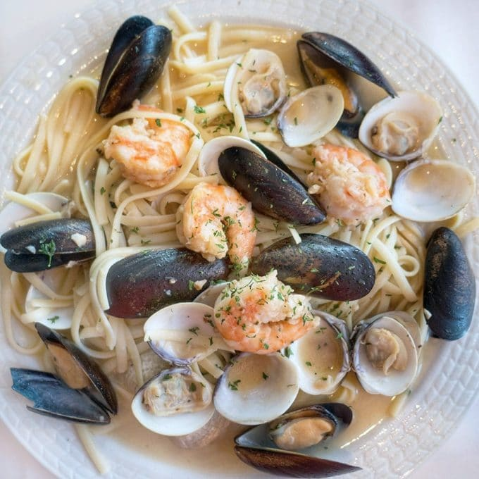 shrimp, mussels and clams over pasta in a garlic aioli sauce in a white bowl
