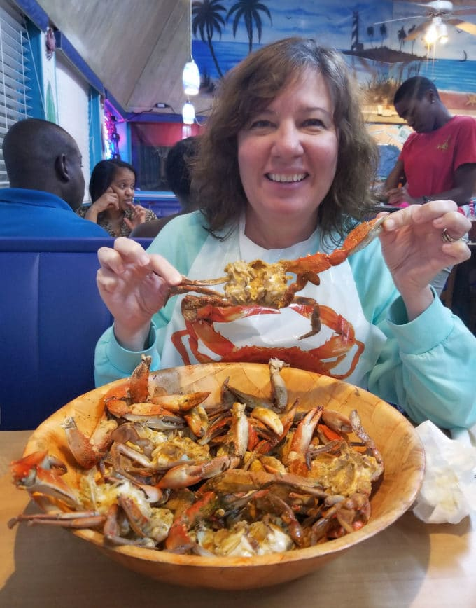 a bowlful of cooked and cleaned crabs with a woman holding up one of the crabs at The Crab Stop in Daytona Beach