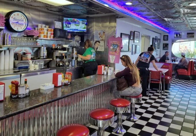 starlite diner in Daytona beach with black and white checkered floor, red top stools and a metal counter top with a woman sitting at the counter, booths in the background with people working