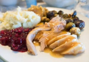 sliced turkey with gravy, cranberry sauce, mashed potatoes, stuffing and brussels sprouts on a white plate