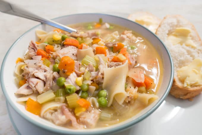 turkey noodle soup in a white bowl with a spoon sticking out on a white plate with bread and butter