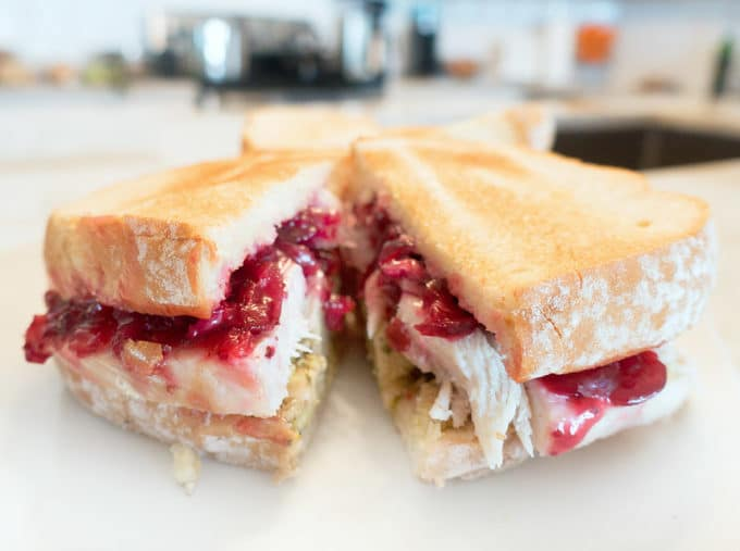 Turkey sandwich on toast with stuffing and cranberry sauce, sliced in half on a white plate