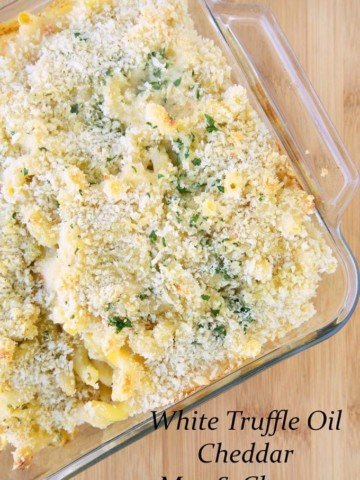 white truffle oil cheddar mac and cheese with parsley and bread crumbs in a baking dish, sitting on a cutting board