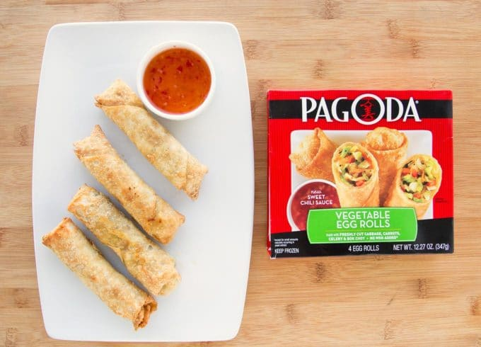 egg rolls and dipping sauce on a white plate with a retail package of Pagoda Egg rolls next to it on a cutting board