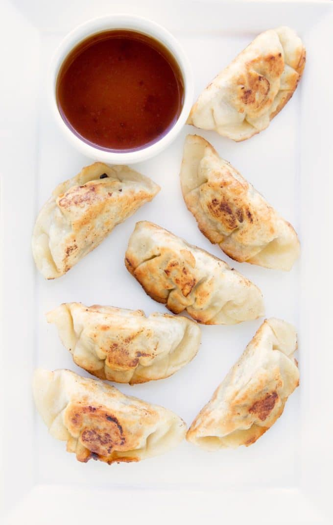 pot stickers and a dipping sauce sitting on a white plate