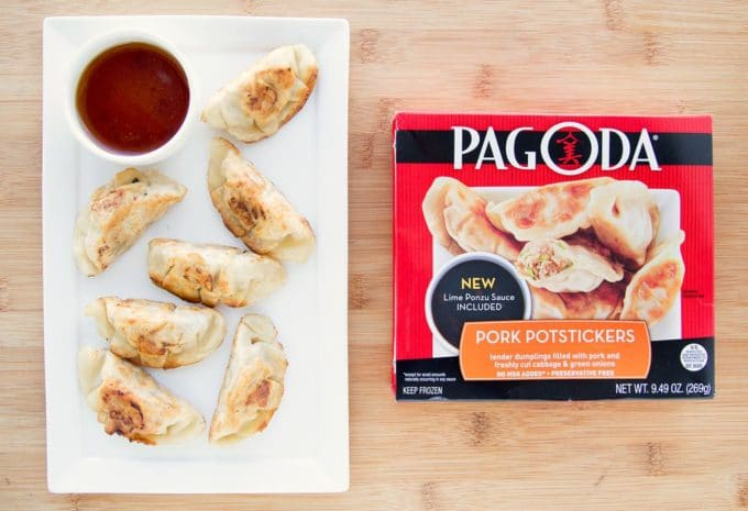 pot stickers and a dipping sauce on a white plate next to a retail package of Pagoda pot stickers sitting on a cutting board