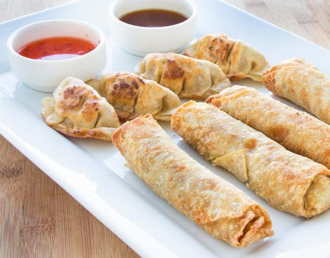 pot stickers and egg rolls on a white tray with dipping sauces